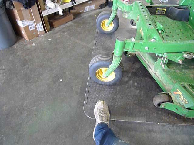 zero turn lawn mower being put on quakermayd lift