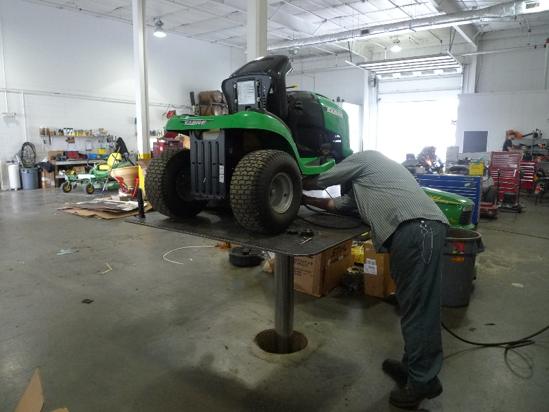 riding tractor being worked on with quakermayd lift help