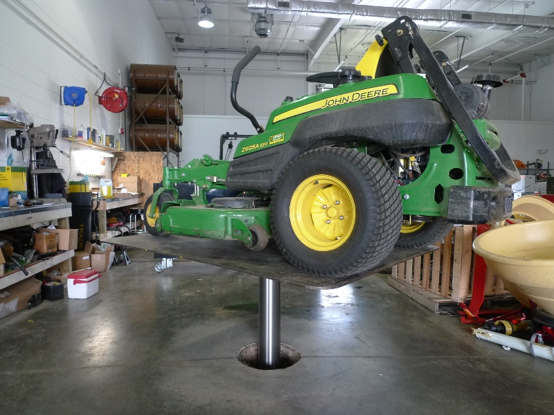 rotated quakermayd lift with riding lawn mower on it