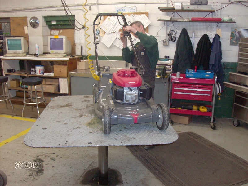 push lawn mower being fixed on quakermayd lift