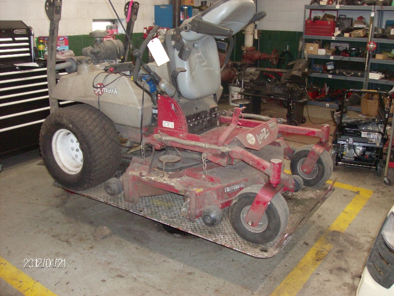 riding lawn mower being repaired on quakermayd lift