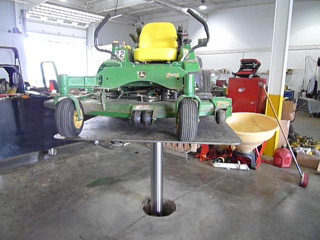 green riding lawn mower elevated on quakermayd lift